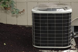 Free standing air conditioner in the exterior back of a home used to cool the house interior in the summer heat.